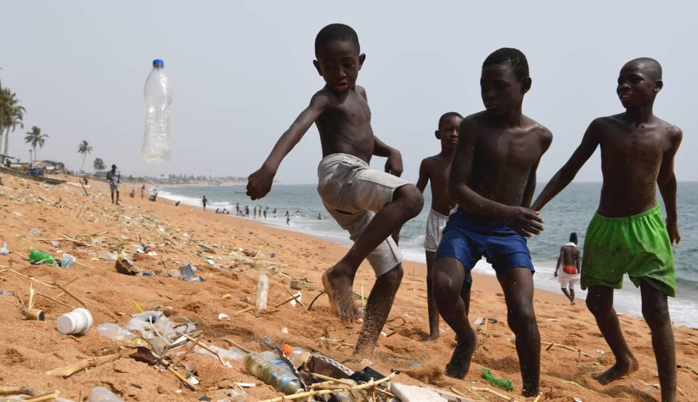 Un grupo de niños juega con una botella de plástico en una playa de Costa de Marfil.