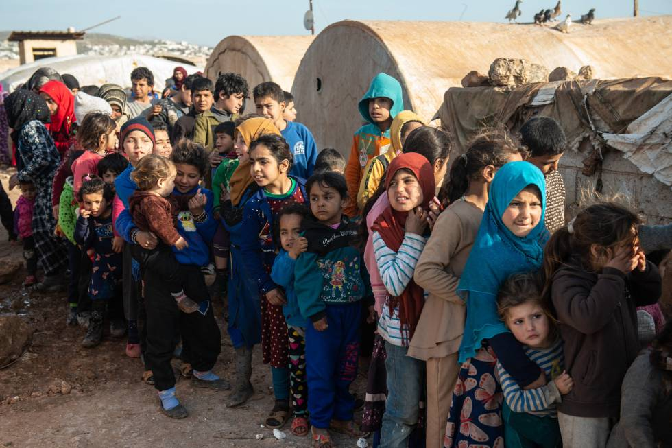 Niños refugiados sirios hacen cola para recibir alimentos en un campamento en la provincia de Idlib.