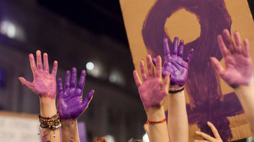 Varias manos pintadas de morado en una manifestación del 8 de marzo.