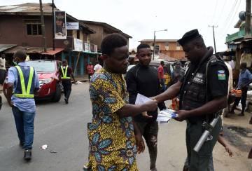 Un policía distribuye información en una calle de Lagos, Nigeria.