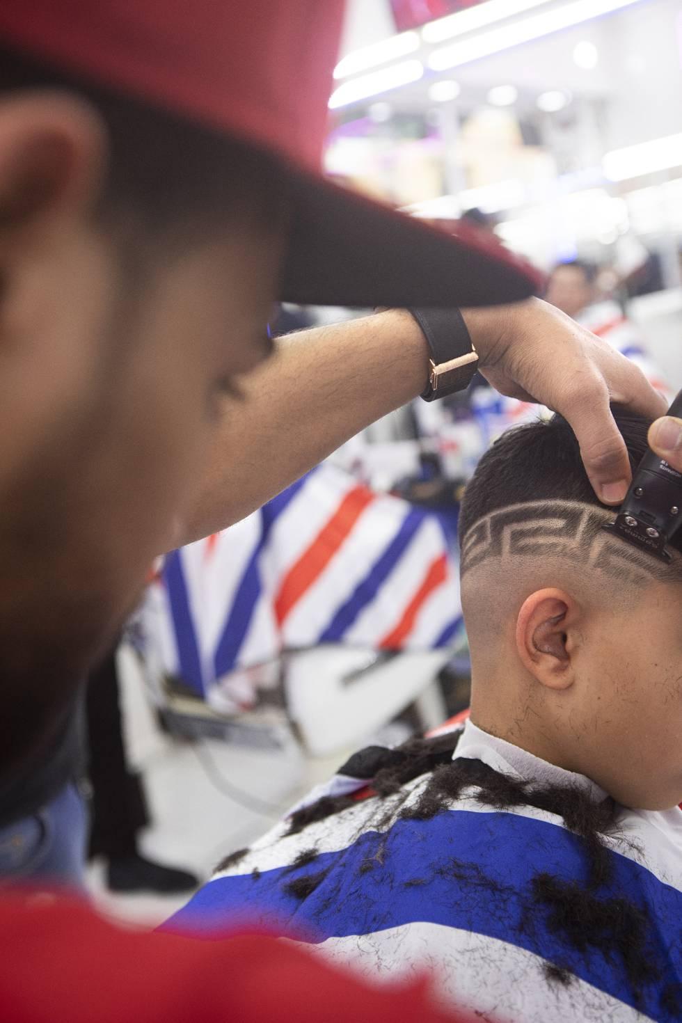El interior del salón de belleza New York (Usera, Madrid), donde están realizando un afeitado con la técnica 'hair tatoo'.