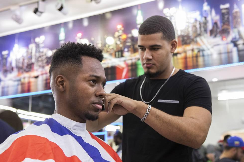 Un empleado de la barbería New York realiza un corte 'undercut', despejado en la nuca y laterales en un degradado.