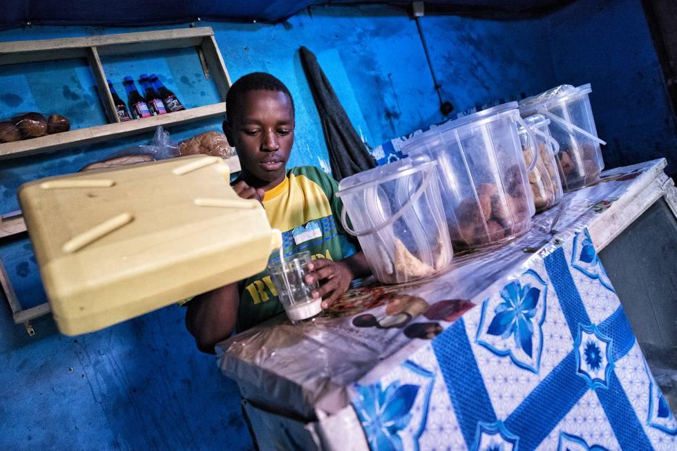 Elie Niyishobora sirve leche de uno de sus bidones junto a los tentempiés que tiene preparados.