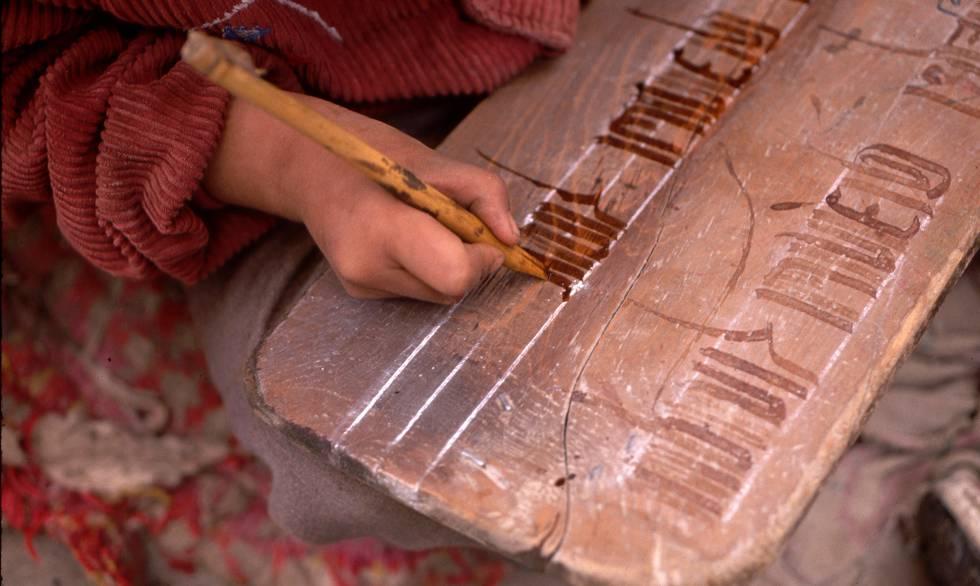 Un niño practica la escritura de caracteres tibetanos en una tablilla de madera.