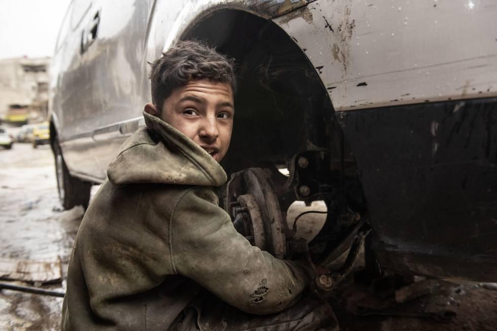 Imad, con 13 años, trabaja en un taller mecánico.