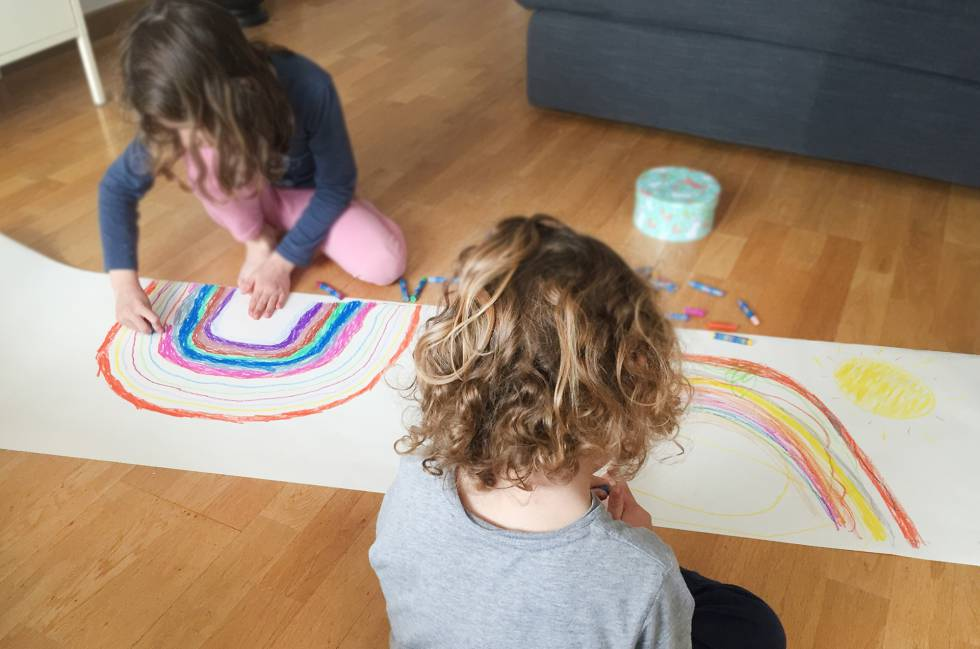 Dos niños dibujan dos arcoíris solidarios.