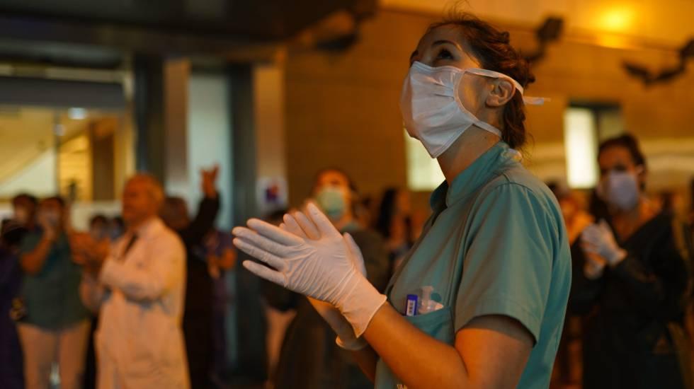 Varios sanitarios aplaudiendo en la puerta del Hospital Infanta Luisa de Sevilla.