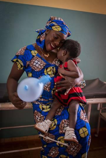 Una madre juega con su hija en el hospital. A la niña le acaban de poner un aparato ortopédico para corregir deformaciones en sus pies.