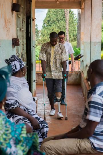 Tras obtener la prótesis, los pacientes deben aprender a andar con ellas, un proceso que requiere su tiempo. En la imagen, un chico da sus primeros pasos ayudado por las muletas.