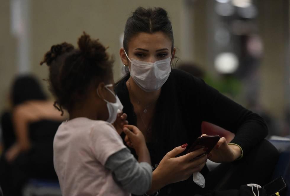 Una mujer y una niña con mascarilla en el aeropuerto Galeão de Río de Janeiro.