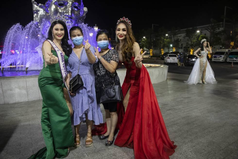 Dos bailarinas de cabaret posan con turistas con mascarillas en Tailandia, uno de los países con más enfermos de coronavirus del sudeste asiático.