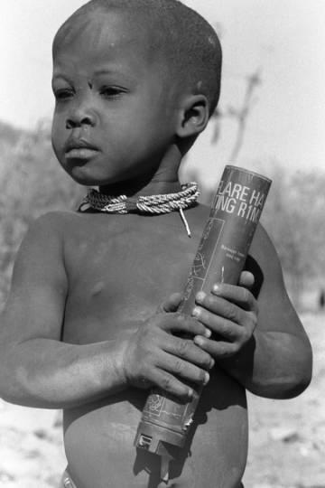 Un niño sostiene una bengala gastada, norte de Namibia, 1987.