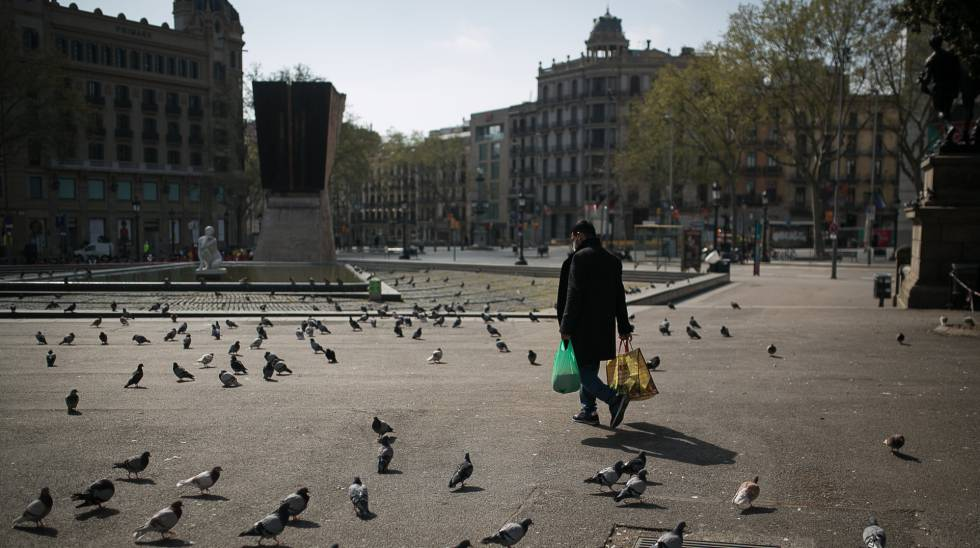 Una persona camina cargado con la compra por plaza Catalunya donde solo quedan las palomas.