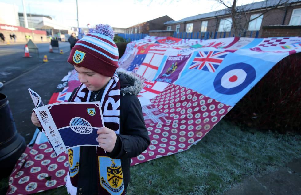 Un niño examina el programa del partido del Burnley FC contra el Leicester City frente a un simpático mural de expresión nacionalista