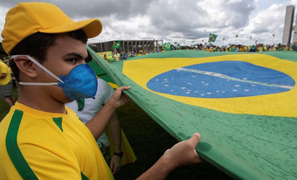Un joven con mascarilla sujeta la bandera de Brasil en la manifestación.