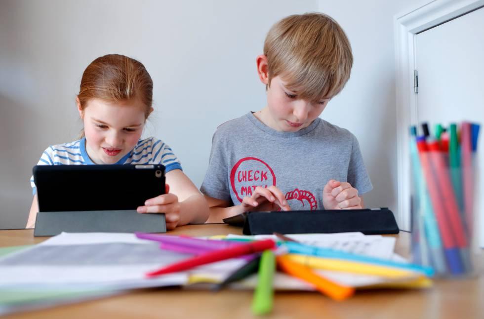 Dos niños realizan tareas escolares a través de sus tabletas electrónicas.