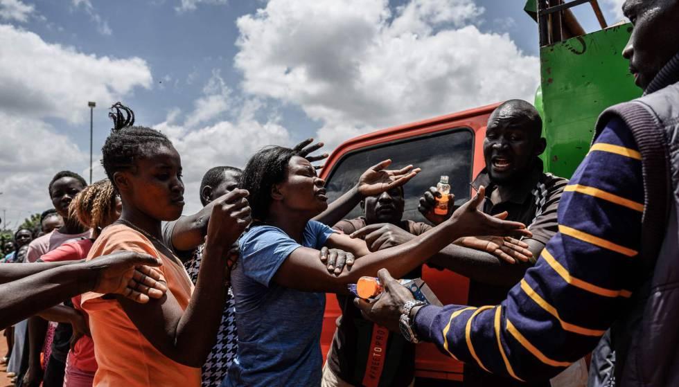 Una mujer recibe alimentos el 2 de abril de 2020, durante una distribución de un grupo de voluntarios kenianos llamados Team Pangaj. Entregan harina, alubias, leche y zumo a unas 900 personas de Kibera, uno de los suburbios más pobres de Nairobi, capital de Kenia.