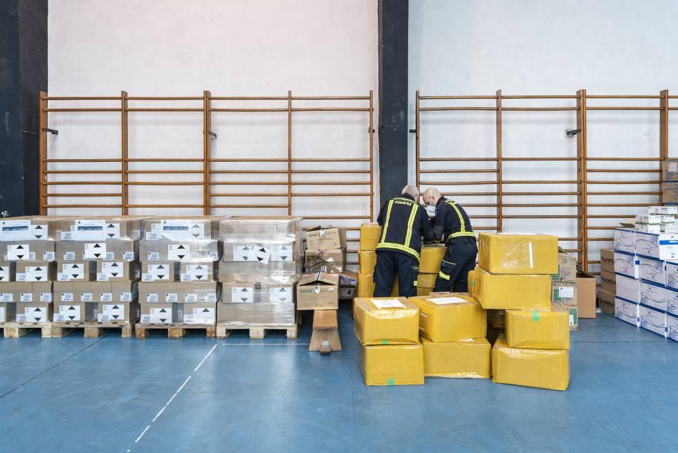 Dos trabajadores en un gimnasio reconvertido en almacén de material sanitario.