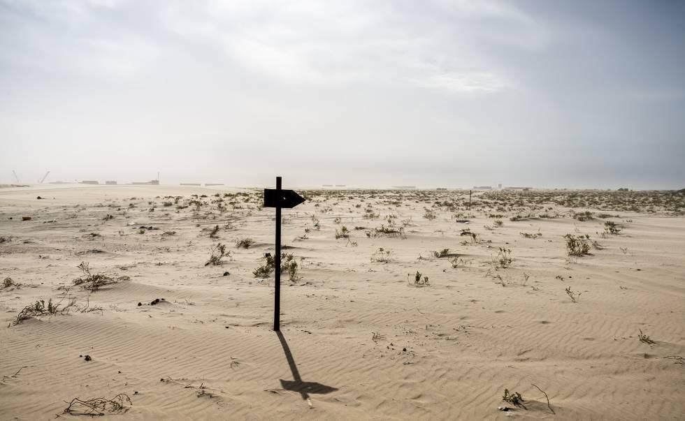 Abajo, una señal clavada en la arena, junto a la vía que recorre Mauritania de norte a sur, mientras se ve al fondo el puerto de Tanit.