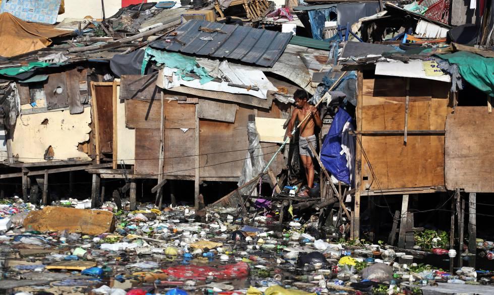 Un hombre escarba entre la basura que cubre el agua de un río al fondo del slum donde tiene su casa, en Pritil, Estero de Vitas, en el distrito de Tondo, en Manila.