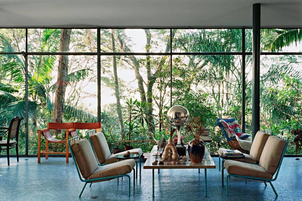 Interior de la Casa de vidrio de Lina Bo Bardi con la vegetación crecida.