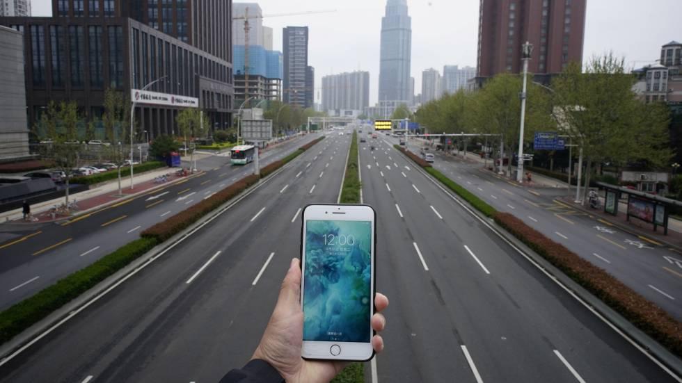 Una persona sostene un teléfono móvil frente a una carretera casi vacía en Wuhan, China, el pasado 31 de marzo.