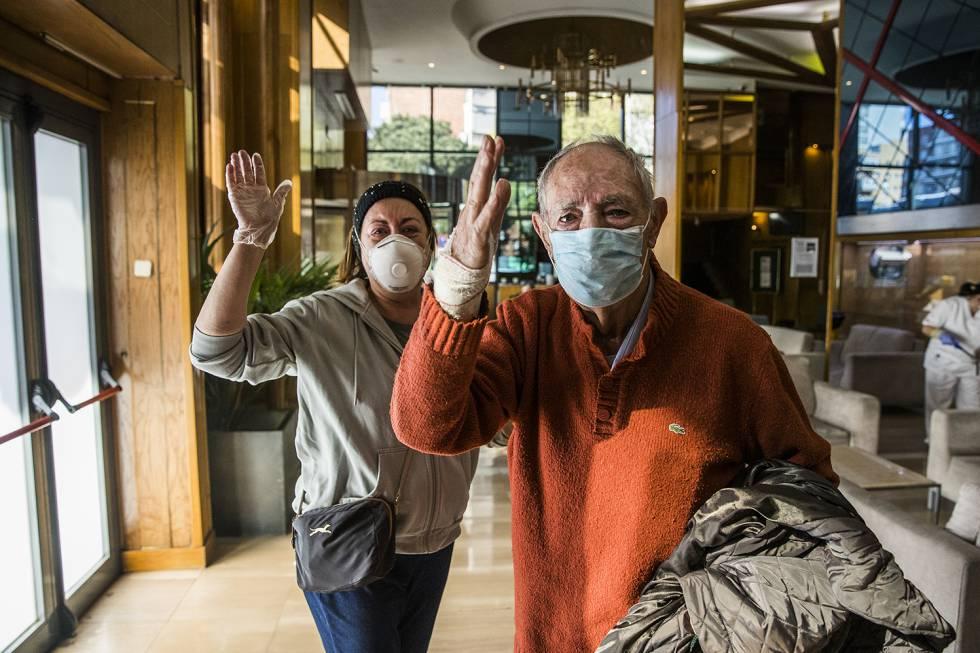 Tras recibir el alta, Francisco Javier Jiménez, de 86 años, se despide de los sanitarios en el 'lobby' del hotel medicalizado de La Paz, junto a su hija Aurora, que ha venido a buscarlo.