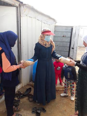 Una voluntaria reparte kits con materiales sanitarios para que las mujeres y las niñas elaboren ellas mismas sus mascarillas en el campamento de refugiados de Azraq.