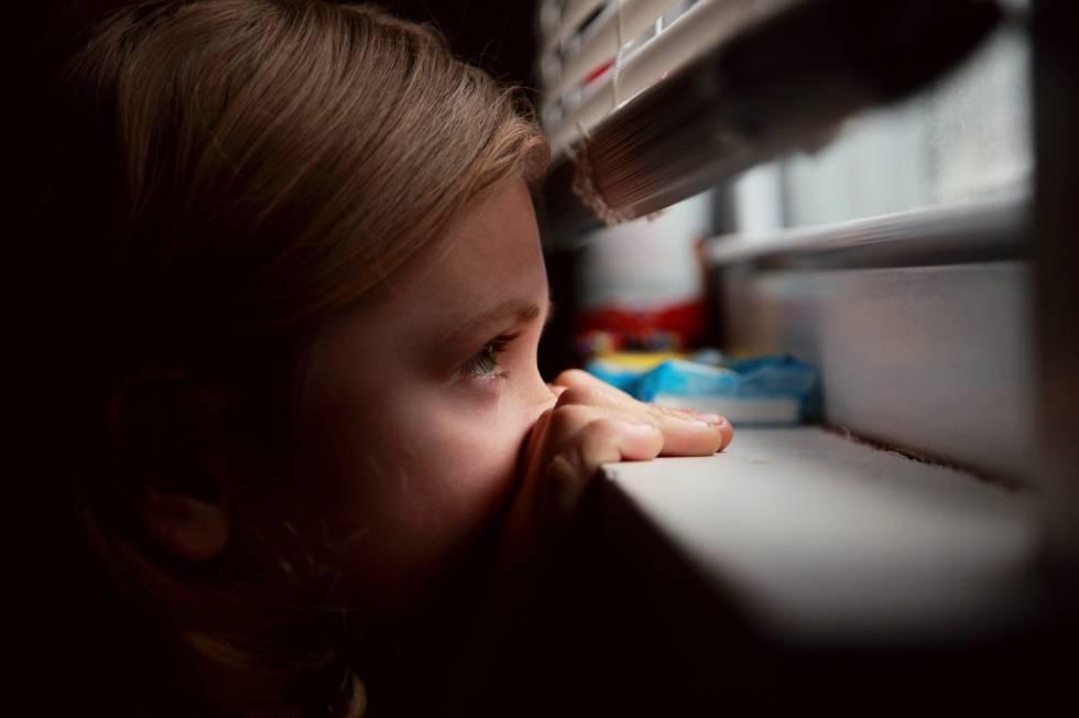 Una niña mira con miedo la calle.