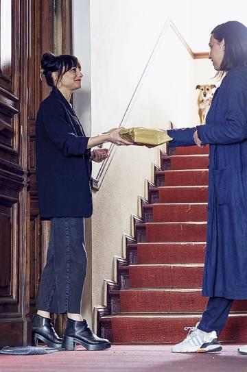 Ana S. Pareja entrega un paquete de libros a domicilio.