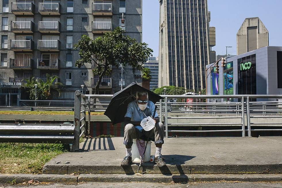 Um homem pede esmola sentado na avenida Libertador, na capital da Venezuela.