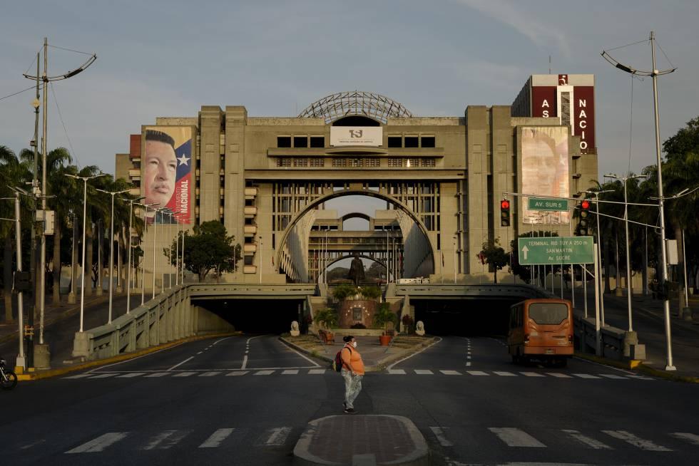 Uma mulher cruza a avenida Bolívar em frente ao Palácio de Justiça em Caracas, Venezuela, o 26 de março de 2020.