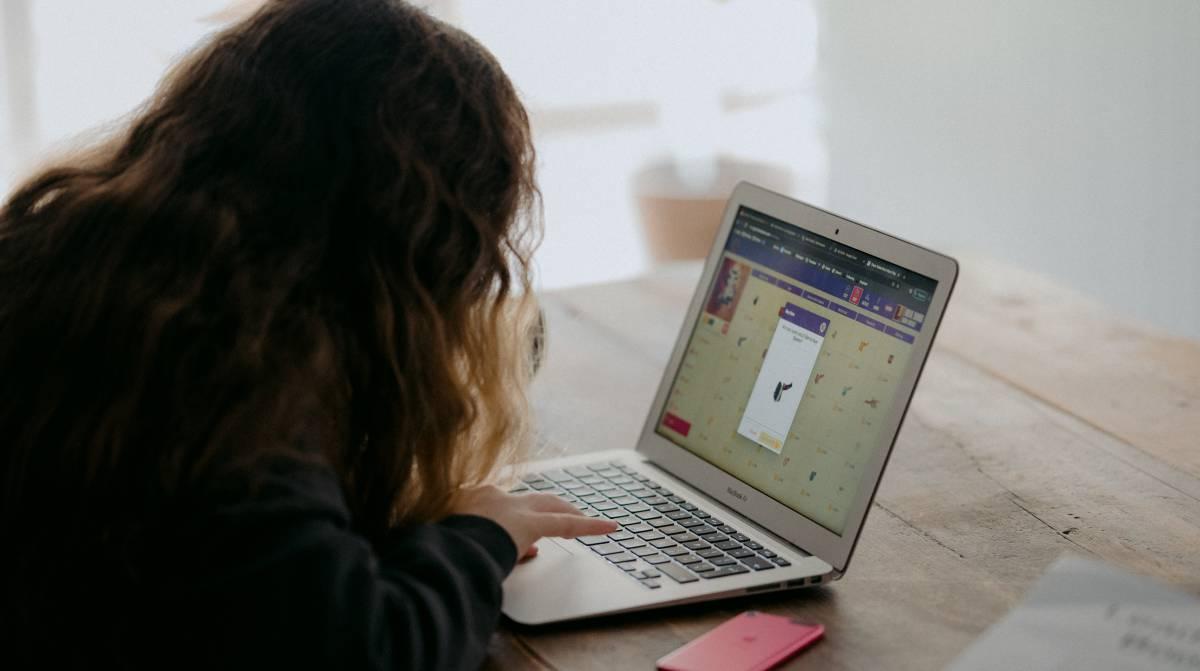 Un niña mira su ordenador en casa.