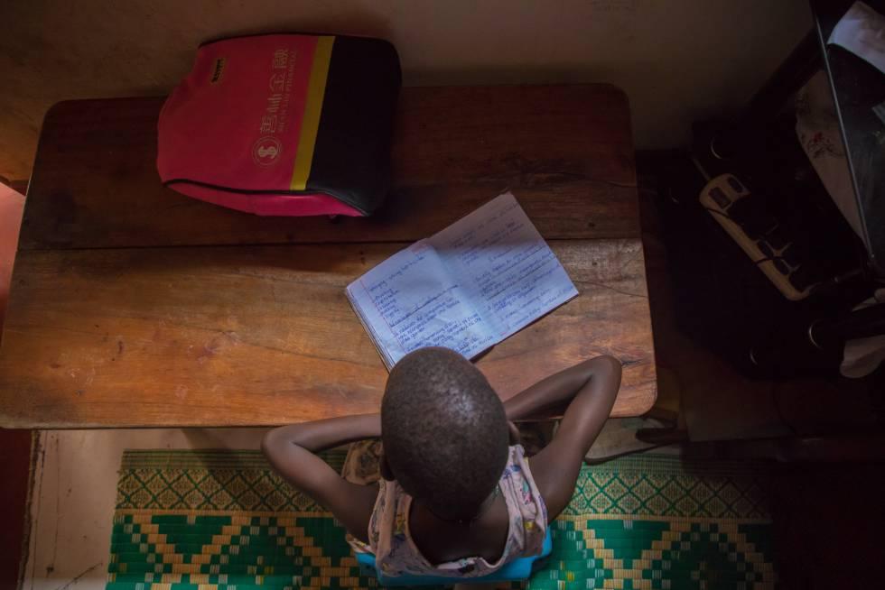 Leticia Amongin, de ocho años, hace los deberes con la poca luz que entra por la ventana de su casa, en Uganda.