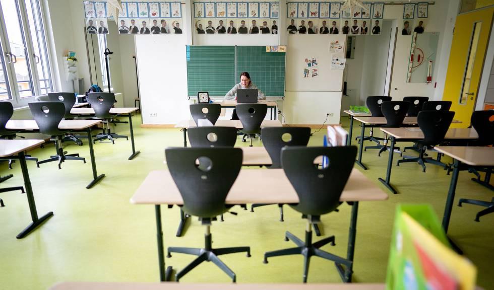 Una profesora da clases por ordenador desde un aula vacía en Alemania.
