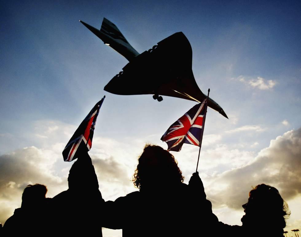 Unos cuantos espectadores agitan banderas británicas en el aeropuerto de Heathrow (Londres) el 24 de octubre de 2003 cuando el Concorde toma tierra en su último vuelo.