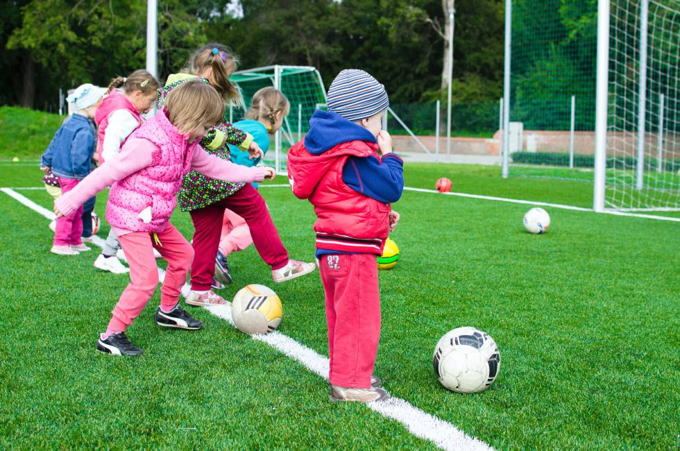 Varios niños juegan al fútbol.