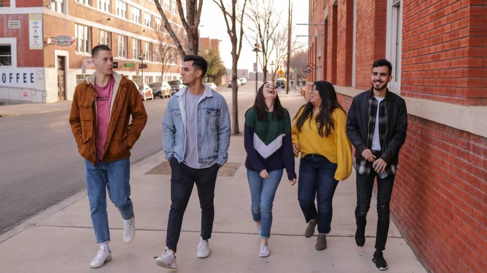 Cinco adolescentes caminan por la calle.