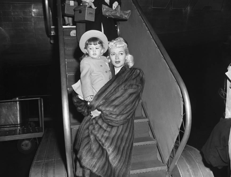 Lana Turner bajando de un avión con su hija Cheryl en brazos en Nueva York en 1946.
