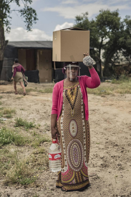 Una mujer de Nigeria porta una caja de alimentos, agua y equipos de protección contra la COVID 19 donados por distintas entidades sociales y ONG en un asentamiento de temporeros en Lucena del Puerto (Huelva).