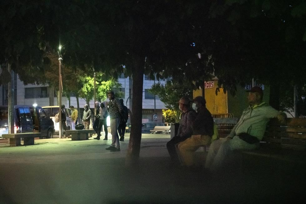 Las furgonetas cargan al alba temporeros en una plaza de Lleida parar llevarlos a los campos de frutas.