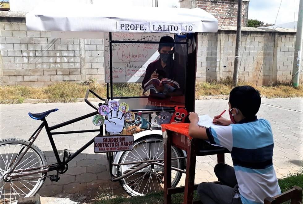 La escuela a pedales de Lalito está separada del estudiante por una varilla de metro y medio y con un cartel informativo sobre la distancia social.