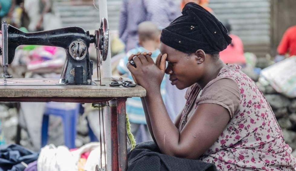 Una costurera del mercado de Majengo, en Goma, mira su teléfono móvil ante la falta de clientes.