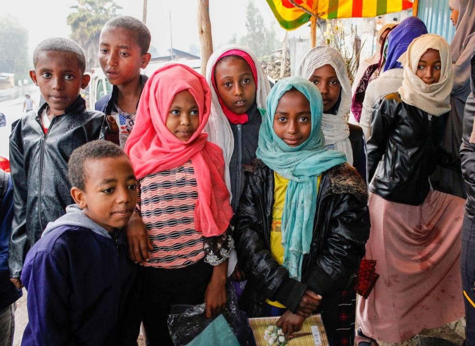 Un grupo de menores se protege de la lluvia bajo un toldo poco antes de empezar la jornada escolar, en una población situada entre Dessie y Weldiya (región de Amhara).
