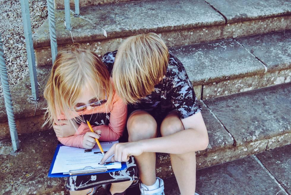 Dos niños estudian juntos en unas escaleras.