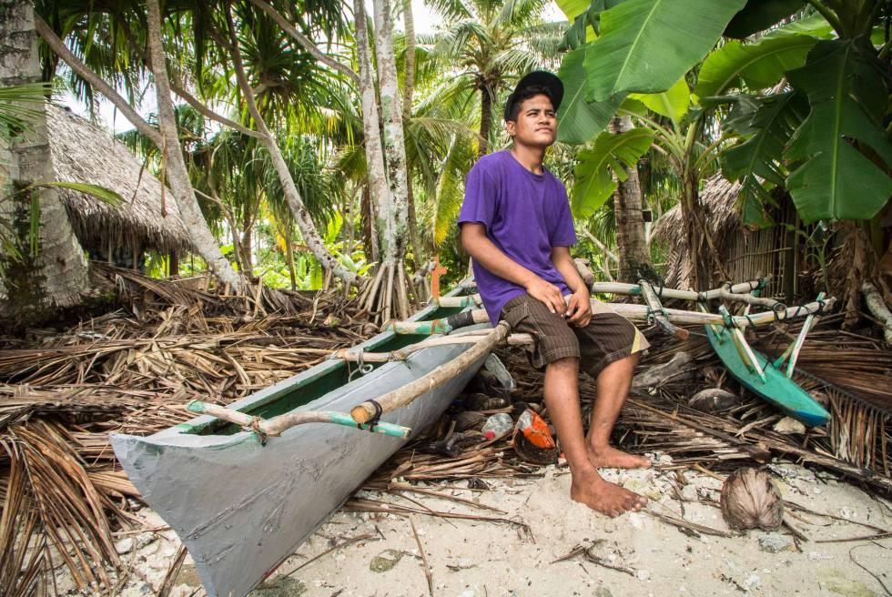 Un joven pescador junto a su canoa.