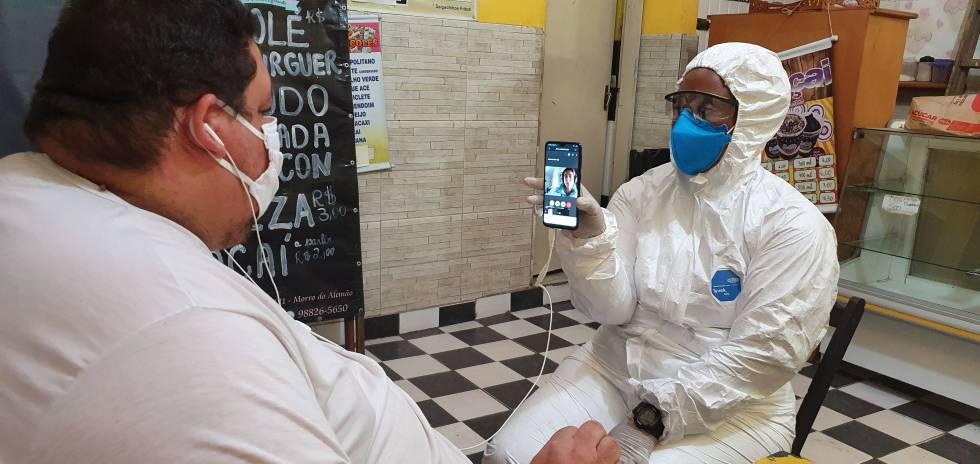 Vecino del conjunto de favelas Complexo do Alemão en teleconsulta médica con una enfermera -que le hace un chequeo básico- del equipo de campo de la asociación civil SAS Brasil. Se encuentran dentro de un local de venta de alimentos, cerrado al público por la pandemia.