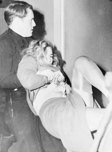 Un polícia detiene a la fuerza a Frances Farmer después de que fuera acusada de atacar a una peluquera dislocándole la mandíbula en 1943.