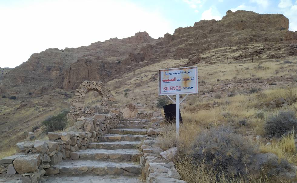 Stairs leading to the entrance of the Mar Musa monastery.  A sign in two languages ​​asks for silence.