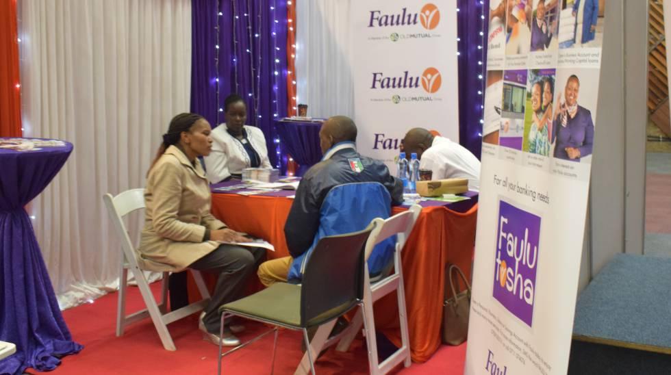 Dos representantes del banco de microfinanzas Faulu habla con dos miembros de una chama durante una feria de negocios en Nairobi, Kenia.